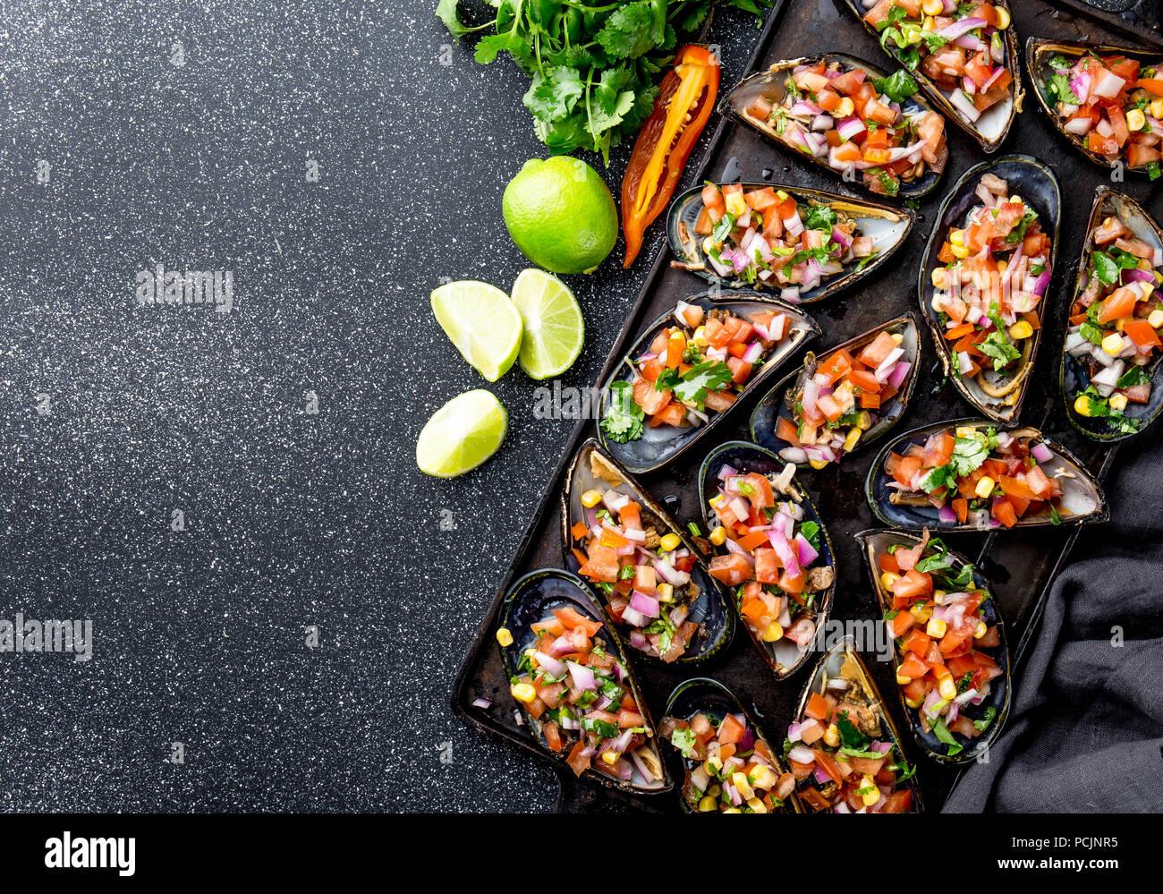 PERUVIAN FOOD. Choros a la chalaca. Big mussels, choros zapatos seasoned with purple onion, tomatoes, corn and lemon. Top view, black background. Traditional peruvian dish - Stock Image