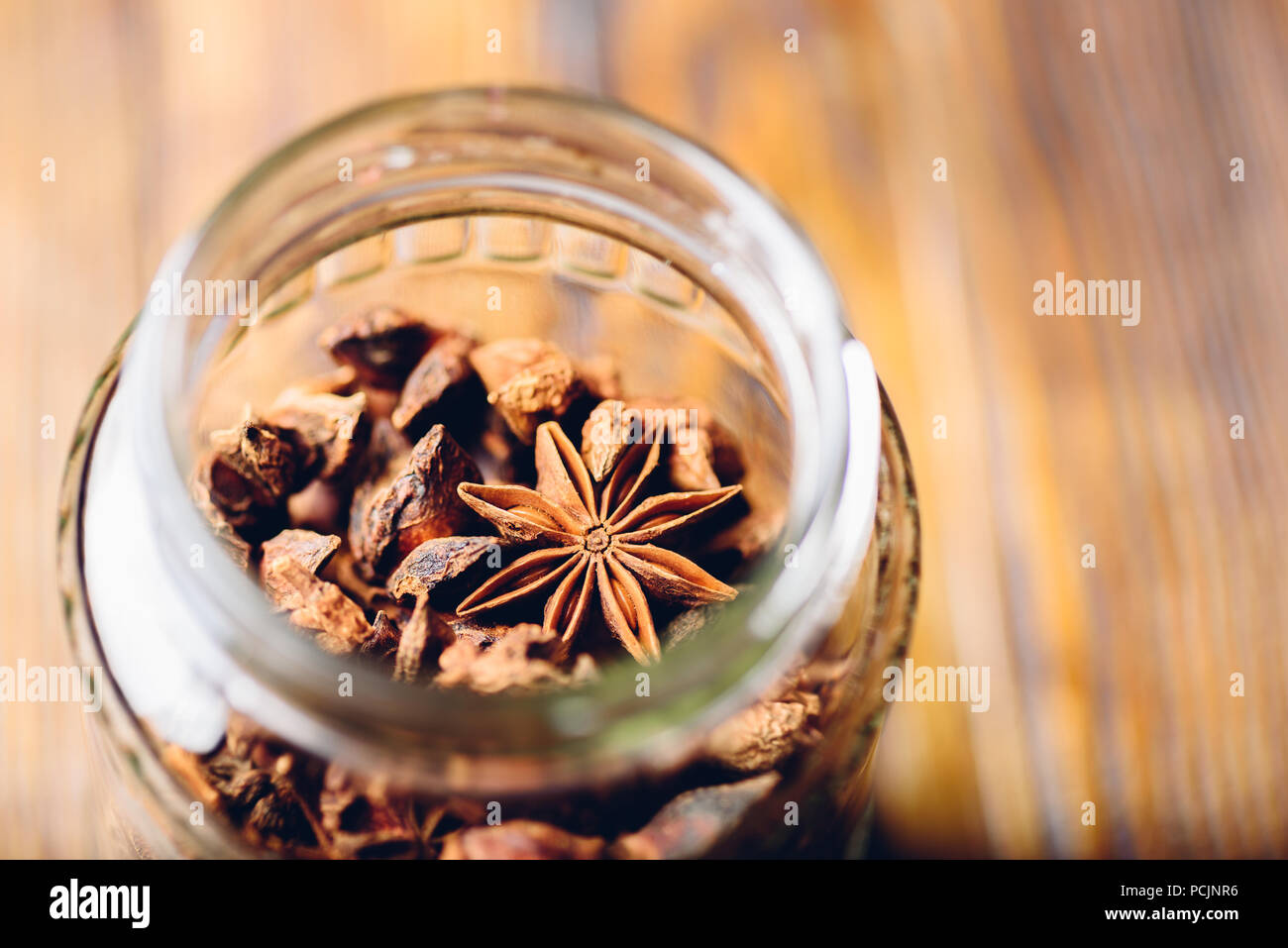 Jar of Star Anise. High Angle View through the Bottleneck. - Stock Image