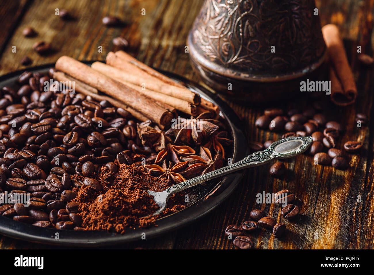 Coffee Beans with Spooonful of Ground Coffee, Cinnamon Sticks and Chinese Star Anise on Metal Plate. Beans Scattered on Wooden Table and Cezve on Back - Stock Image