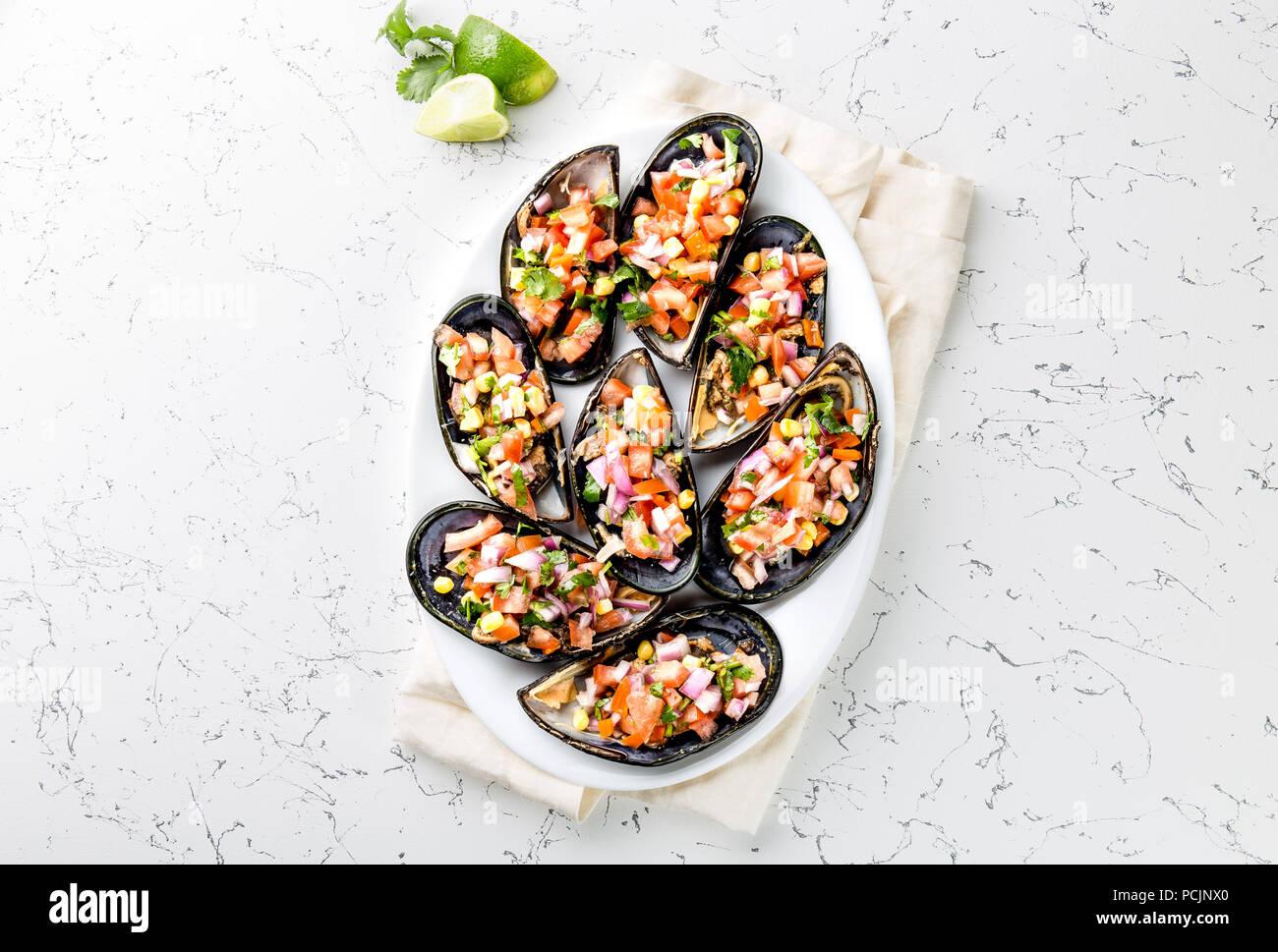 PERUVIAN FOOD. Choros a la chalaca. Big mussels, choros zapatos seasoned with purple onion, tomatoes, corn and lemon. Top view, white background. Traditional peruvian dish - Stock Image