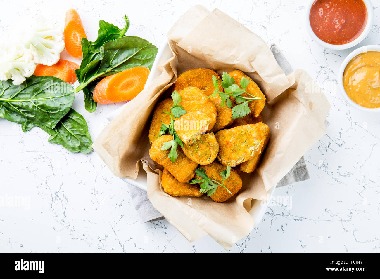 Healthy vegetarian nuggets with carrots, cauliflower and spinach. Vegetable nuggets. Vegan food. Top view, white background - Stock Image