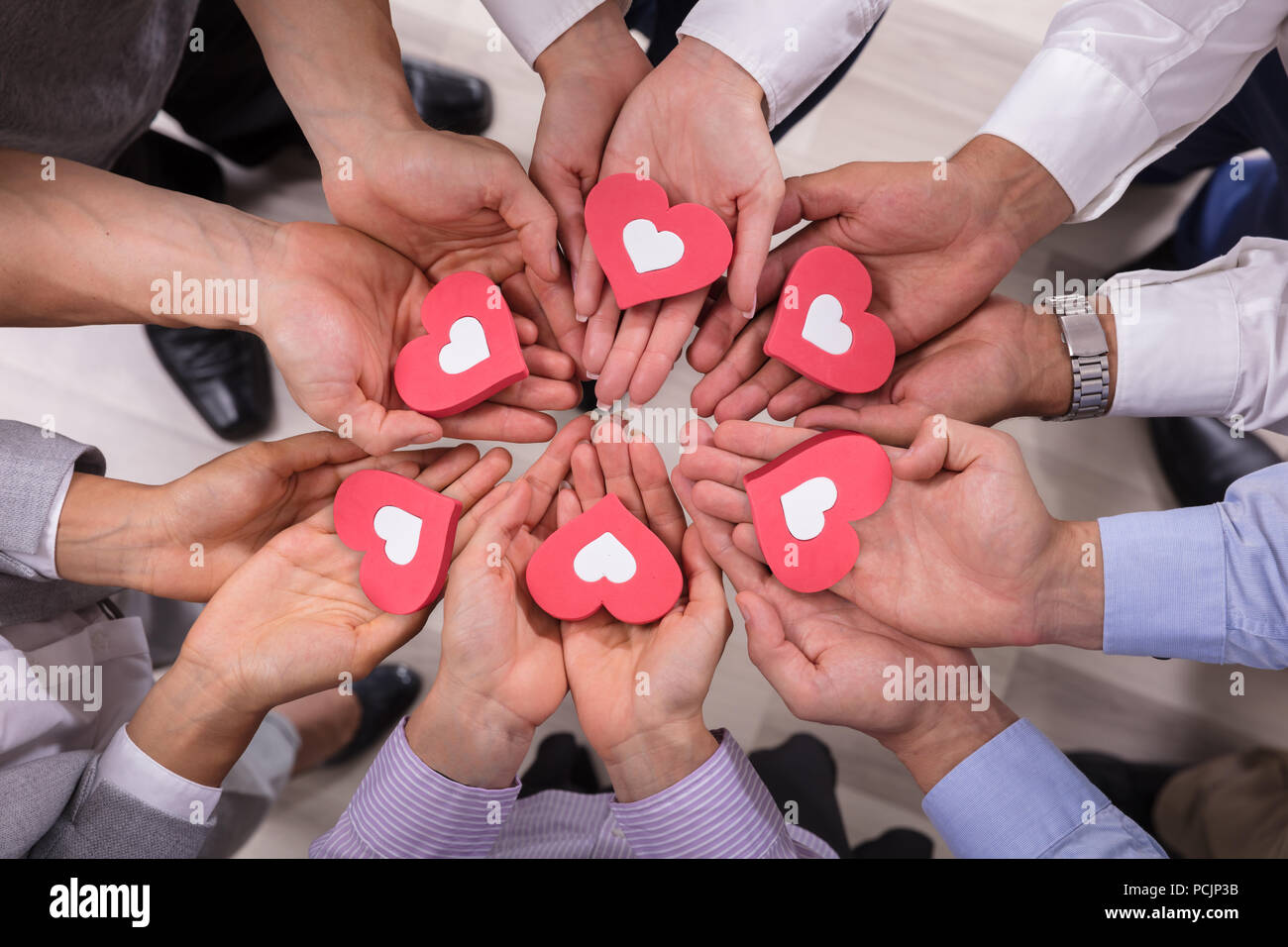 High Angle View Of Businesspeople Holding Red Hearts - Stock Image