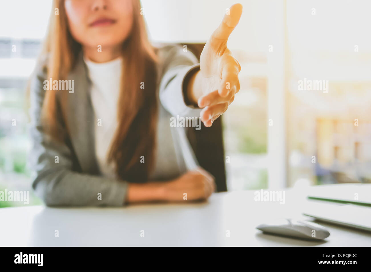 Business woman giving her hand for handshake to partner ,partnership concept - Stock Image