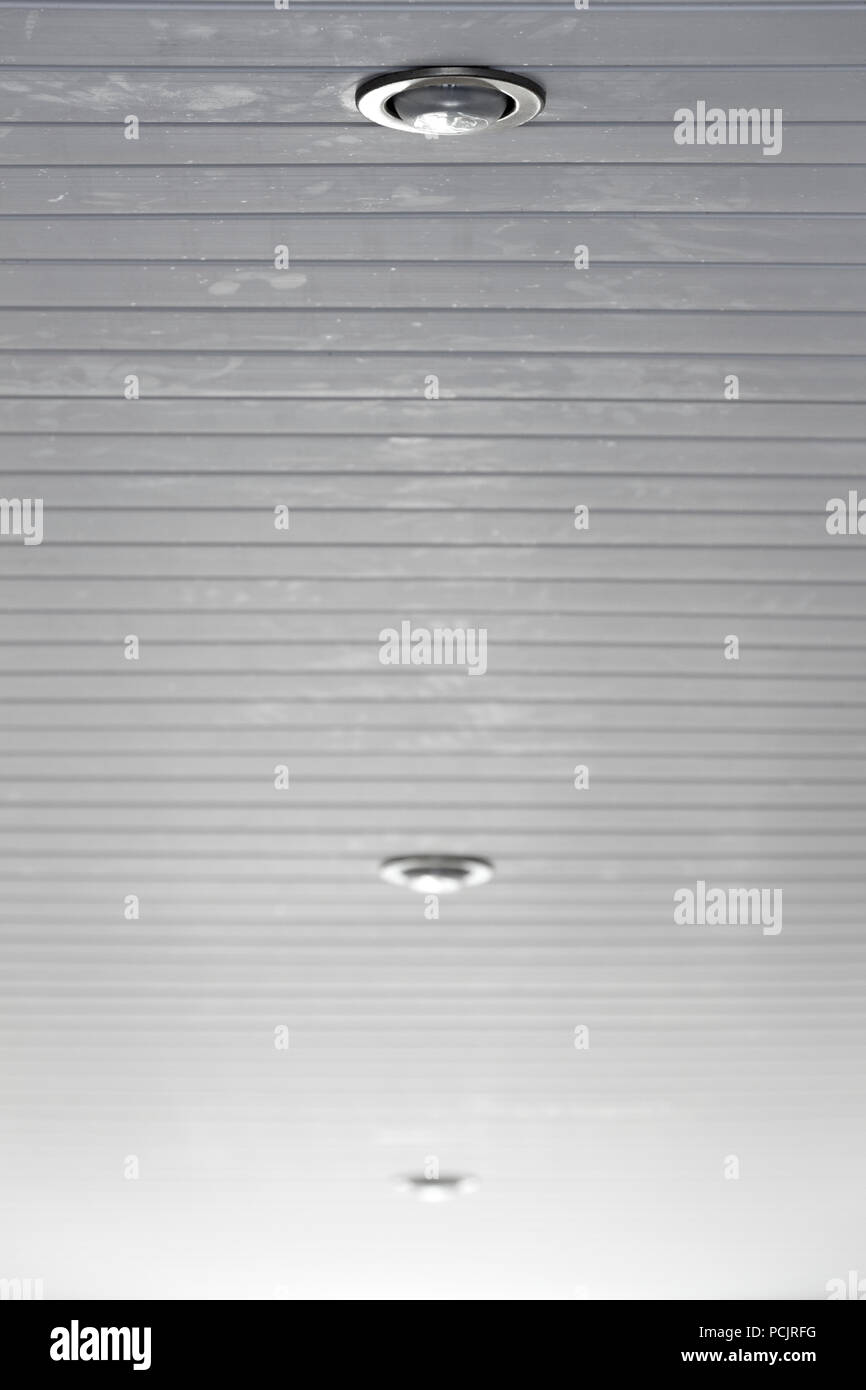 Three recessed luminaires in a hanging plastic ceiling. - Stock Image