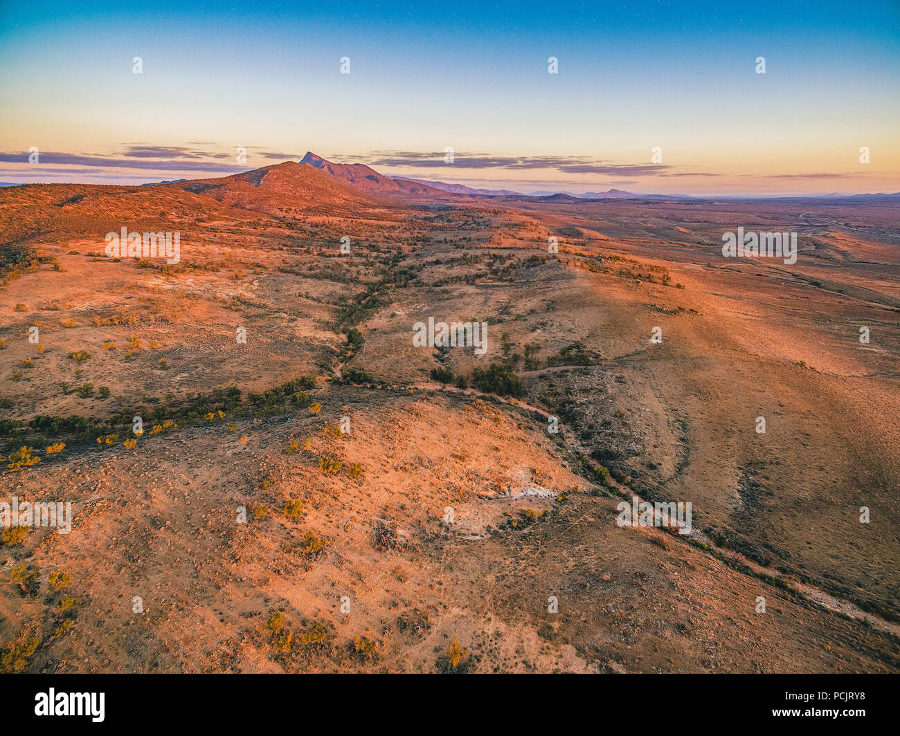 Red hills and rugged peak at sunset in Flinders Ranges, South Australia - Stock Image
