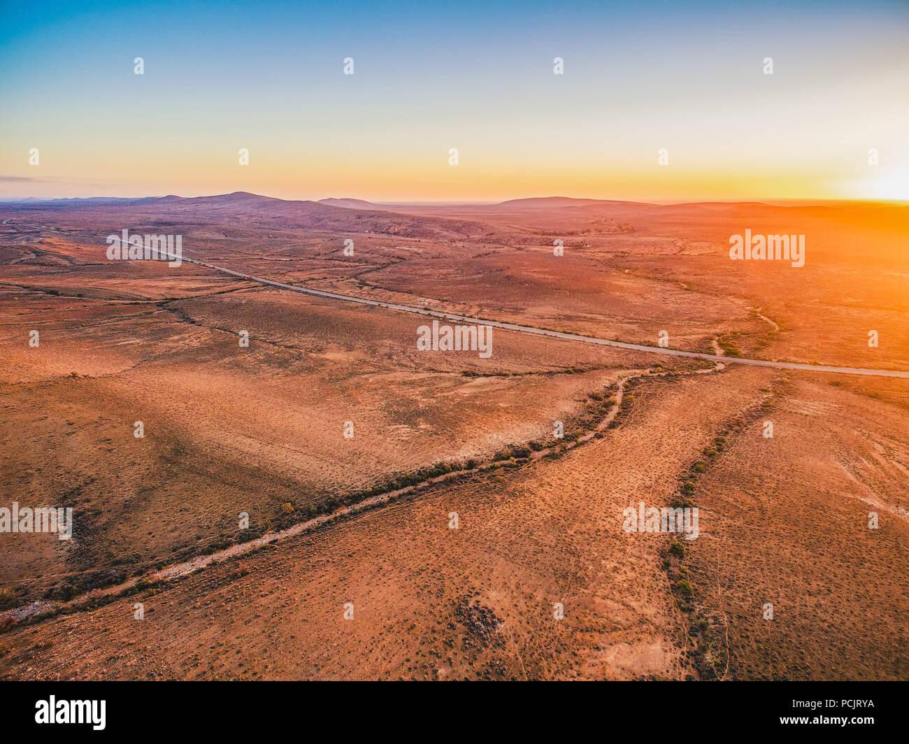 Sunset sun flare over alien landscape of Flinders Ranges in South Australia - Stock Image