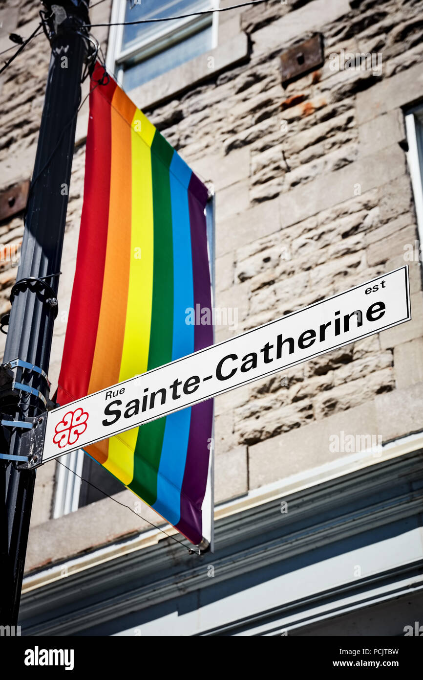 Sainte Catherine street sign and a rainbow flag in gay village of Montreal, Quebec, Canada - Stock Image
