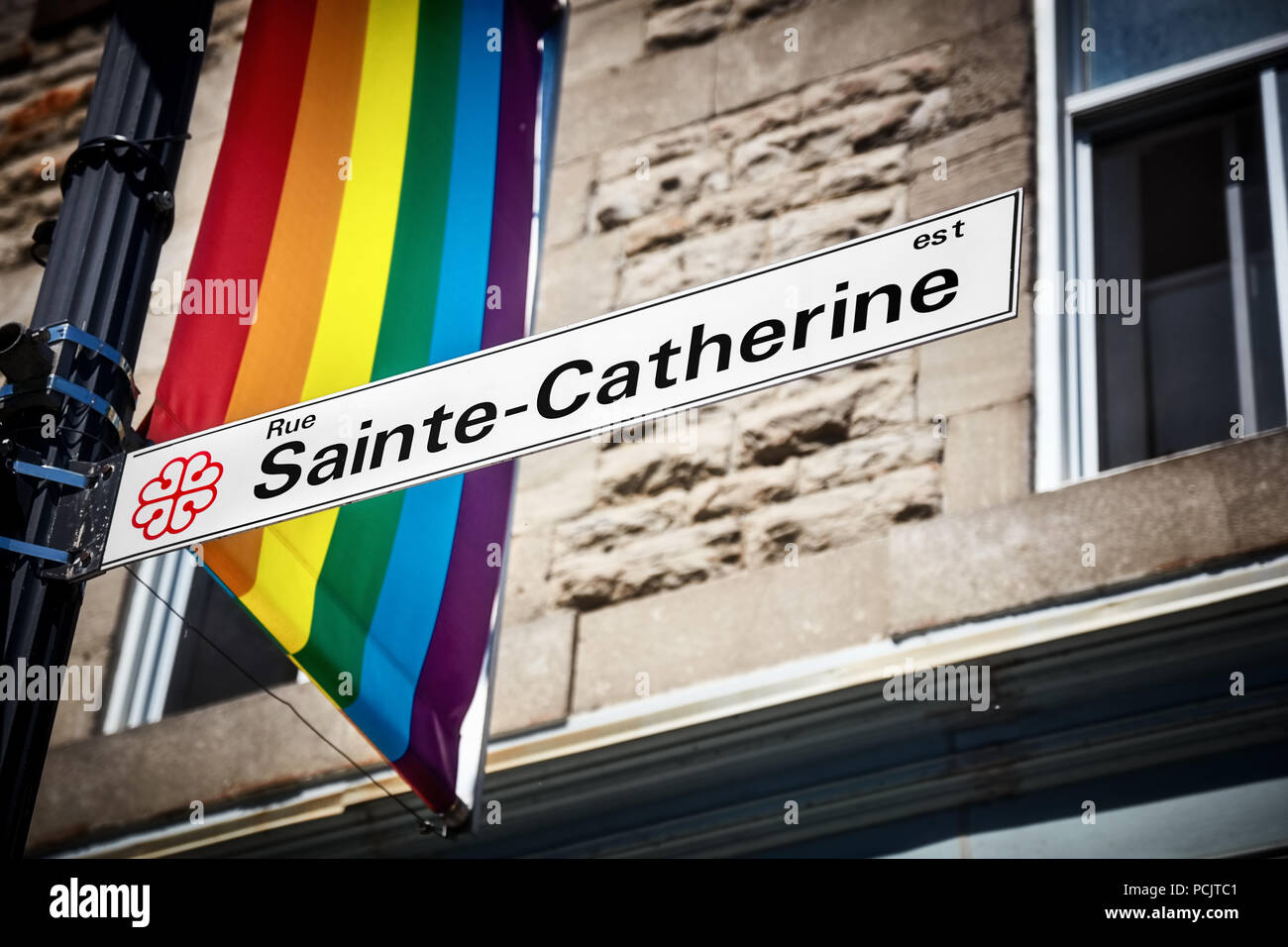 Sainte Catherine street sign and a rainbow gay pride flag in gay village of Montreal, Canada - Stock Image