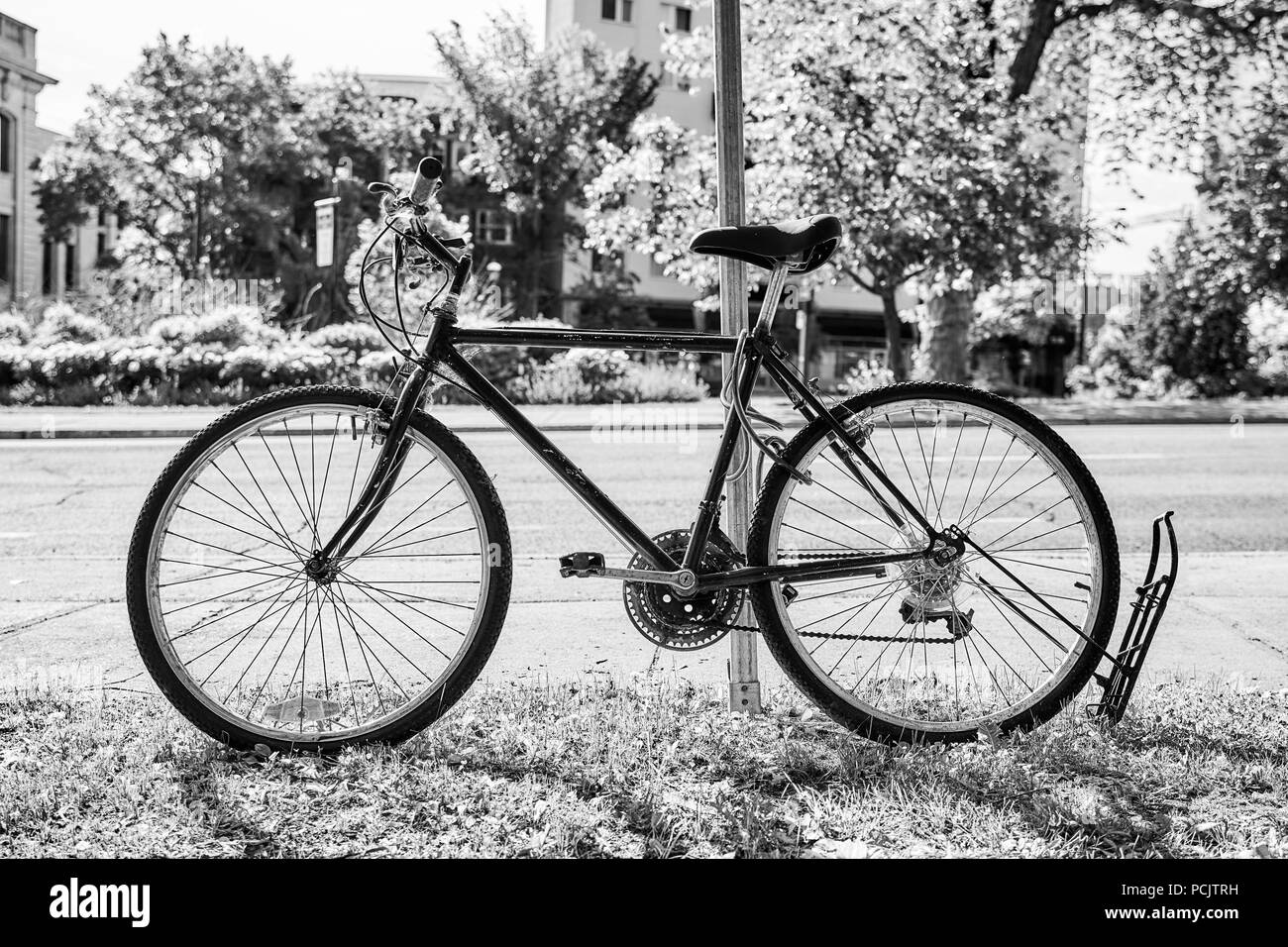 Black and white photo of an old vintage black bicycle parked in a parking rack near the road - Stock Image