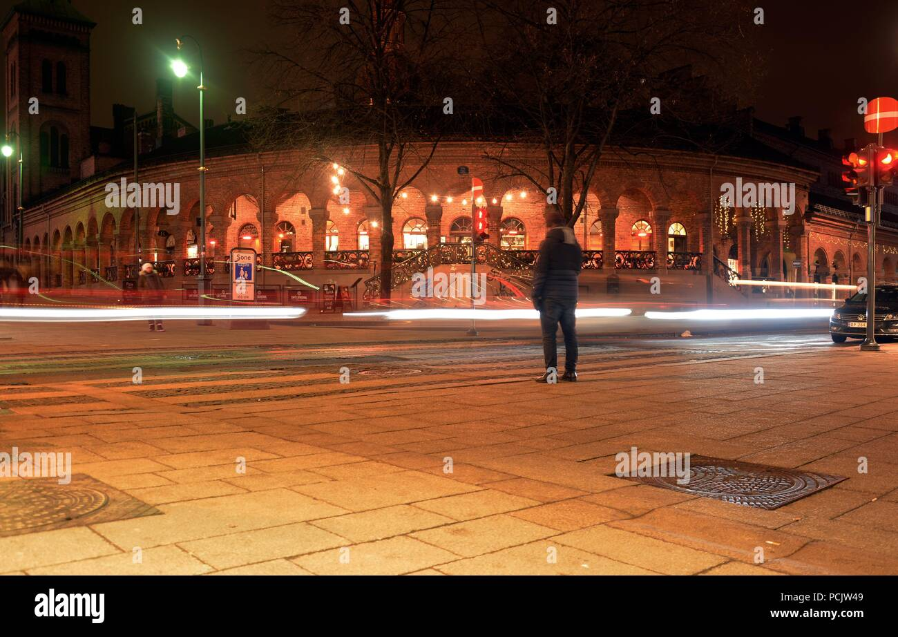 A Man Waiting For The Green Lights To Go Across The Street In Oslo   Stock