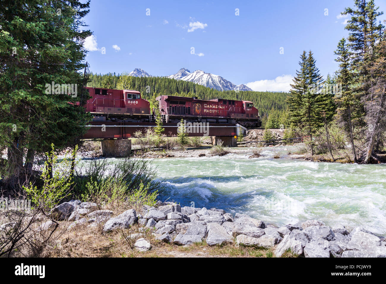 A freight train on the Canadian Pacific Railway crossing the Bow River in the Rocky Mountains at the town of Lake Louise, Alberta, Canada Stock Photo