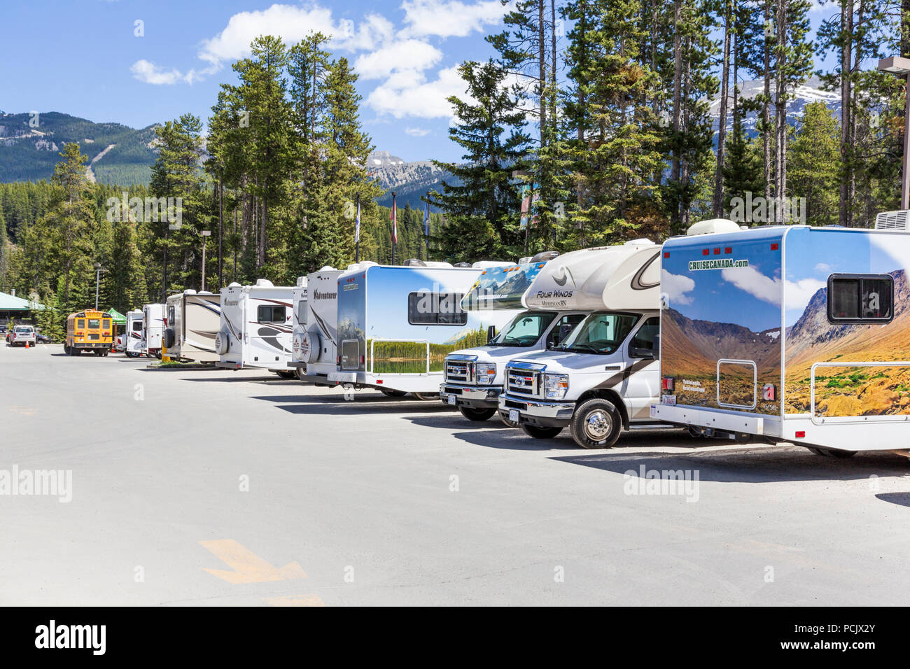 Motor homes in a car park in the Rocky Mountains at the town of Lake Louise, Alberta, Canada - Stock Image