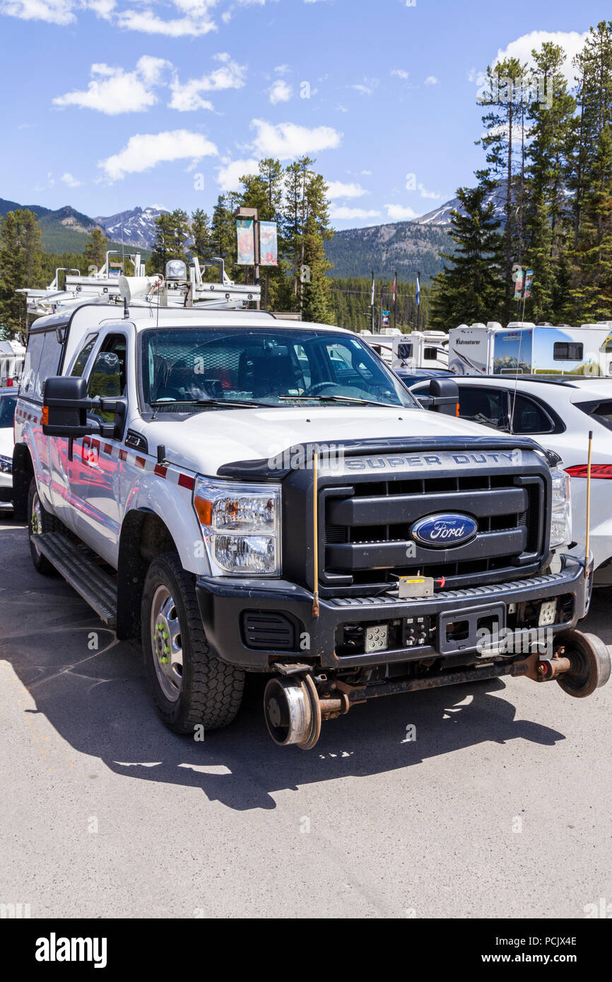 Maintenance truck adapted to also run on railway lines in a car park in the Rocky Mountains at the town of Lake Louise, Alberta, Canada - Stock Image