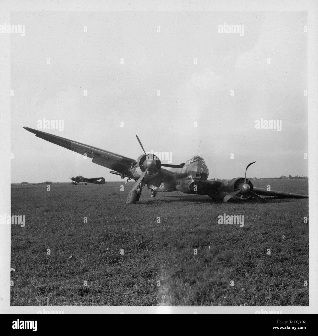 Image from a photo album relating to II. Gruppe, Jagdgeschwader 3: A Junkers Ju 88 of Kampfgeschwader 54, field modified to carry a 20mm cannon in its nose glazing, rests on its collapsed undercarriage on an airfield in Russia in 1941. The 'Totenkopf' (Death's Head) badge of the Geschwader can be seen on the side of the cockpit. - Stock Image
