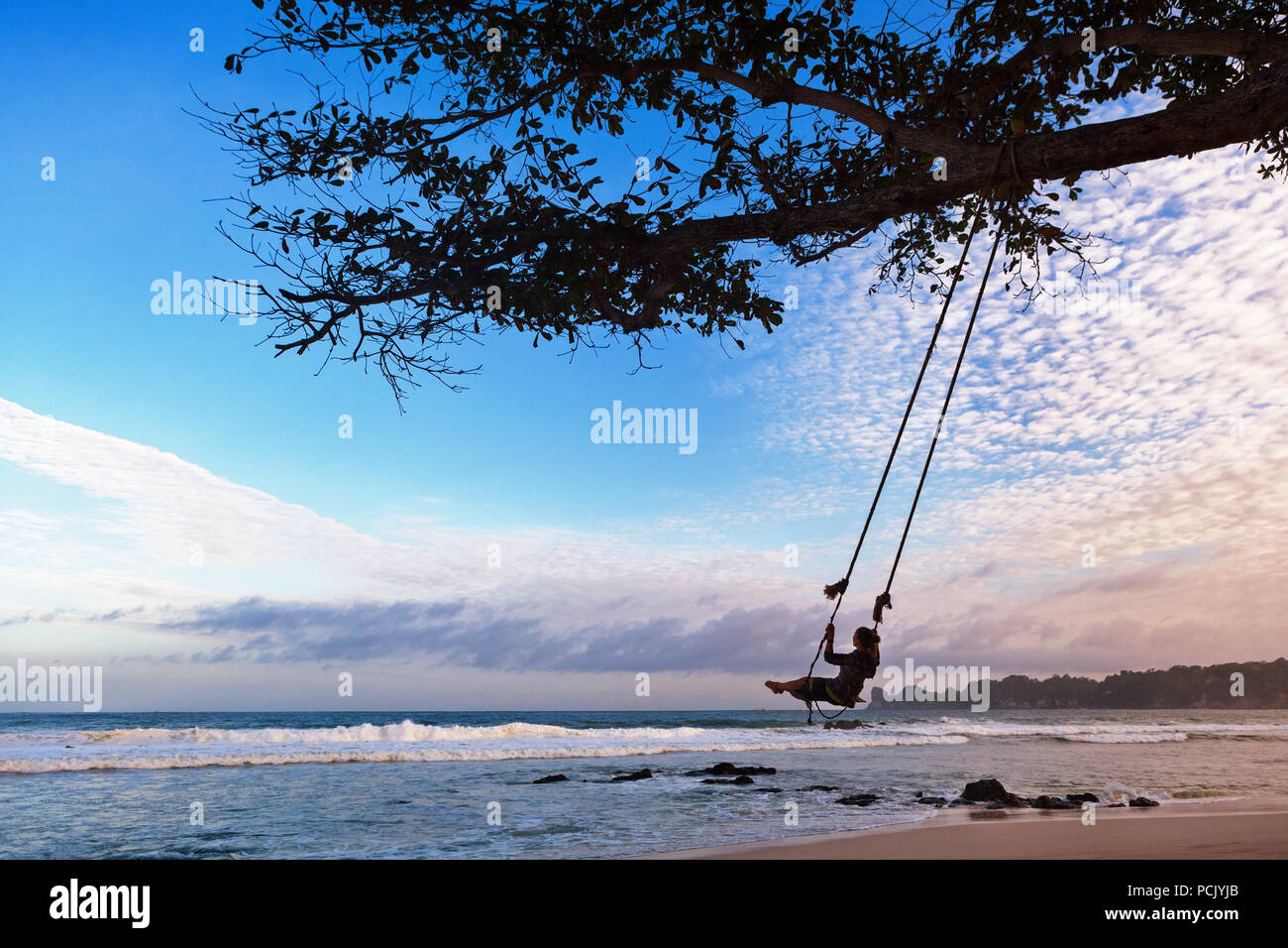 Happy girl have fun swinging high in mid air. Flying up upside down on rope swing on sea beach. Family travel adventure on paradise tropical island. - Stock Image