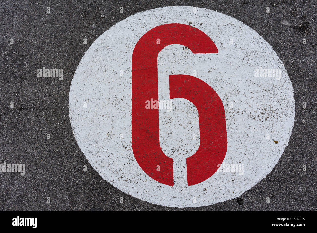 red number in white circle road sign direction on concrete Stock