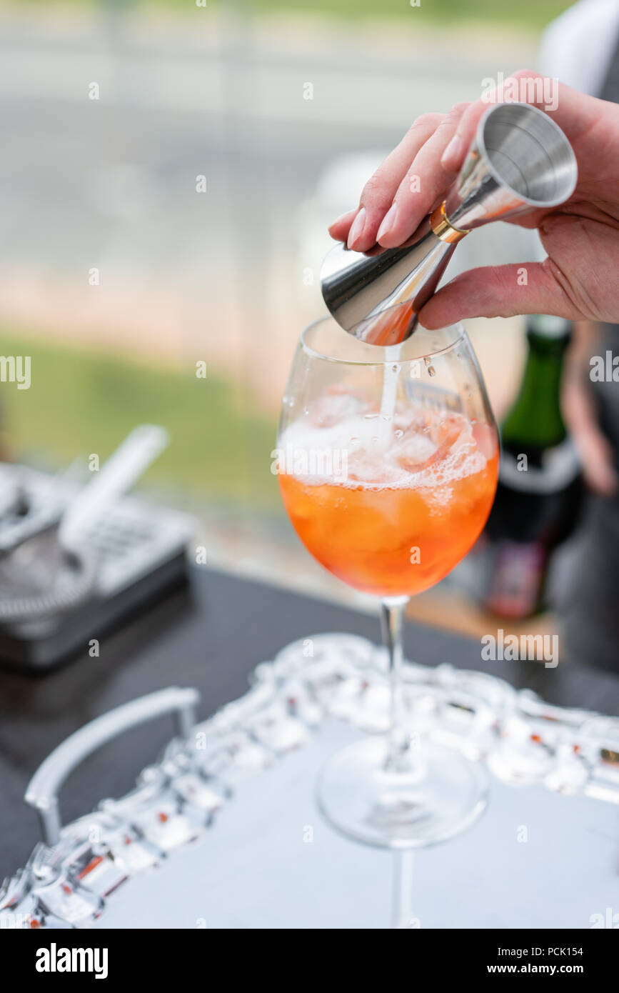 Bartender makes cocktail Aperol spritz. Misted glass, selective focus. Alcoholic beverage based on bar counter with ice cubes and oranges. outdoor party - Stock Image