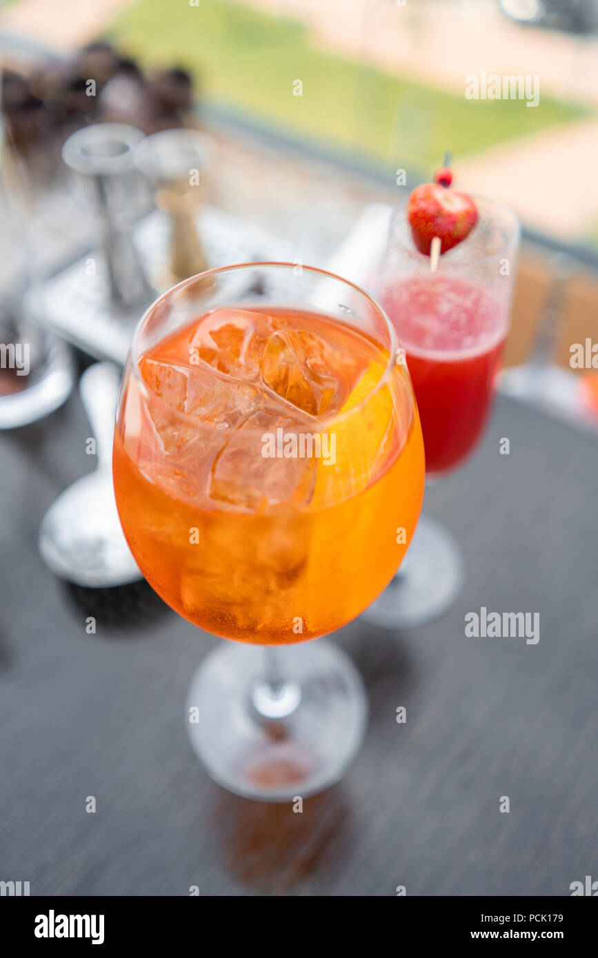 Aperol spritz cocktail in misted glass, selective focus. Alcoholic beverage based on bar counter with ice cubes and oranges. metal shakers in the background Stock Photo