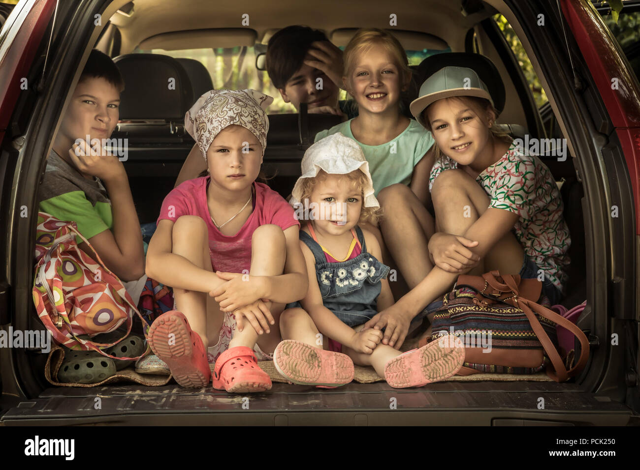 Group of smiling children big family in car trunk luggage