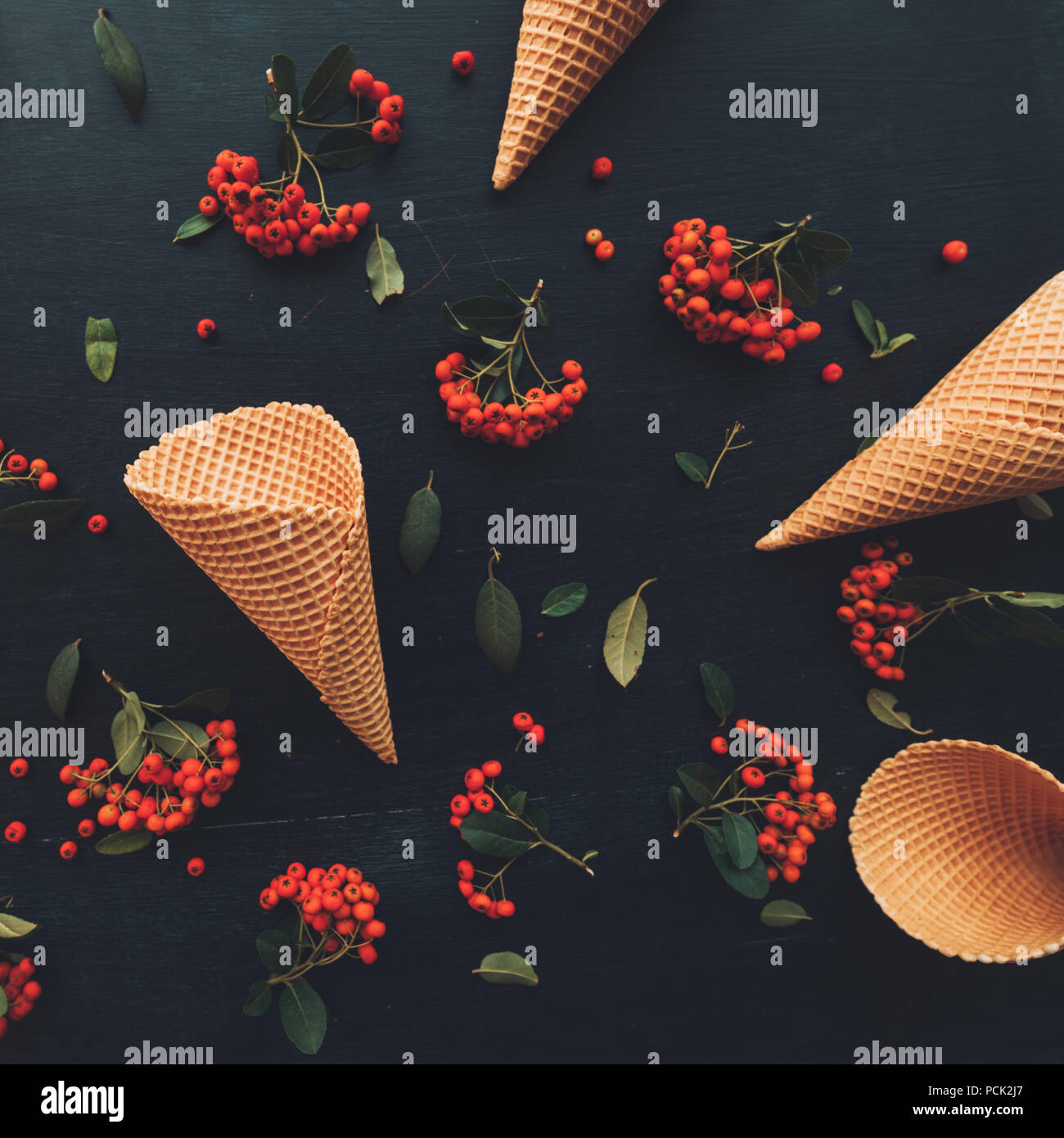 Waffle ice cream cone flat lay top view on dark black wooden background decorated with wild berry fruit arrangement - Stock Image