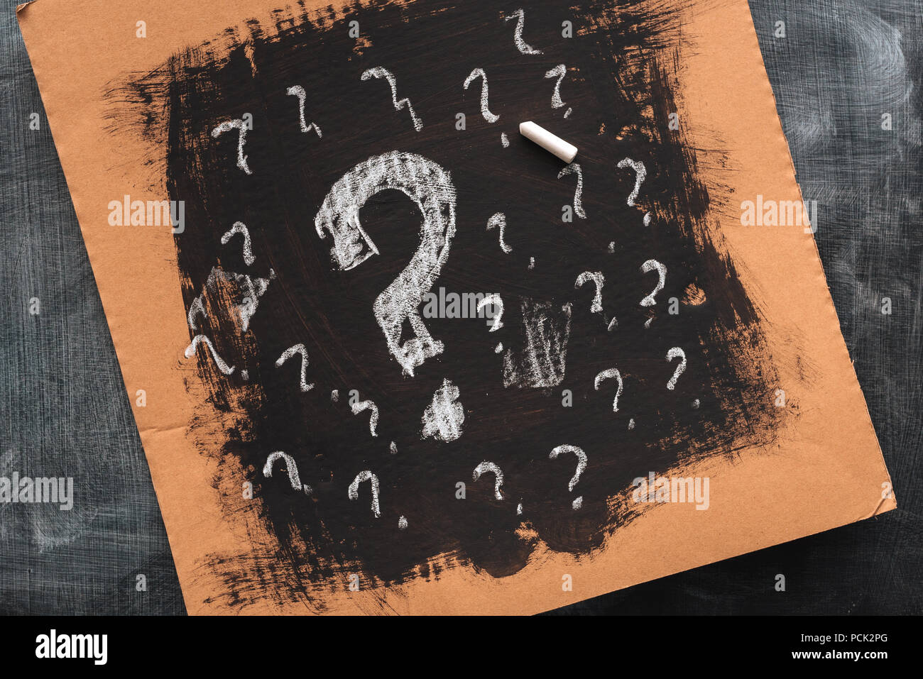 Sketched question marks on cardboard paper, concept of perplex and confusion - Stock Image
