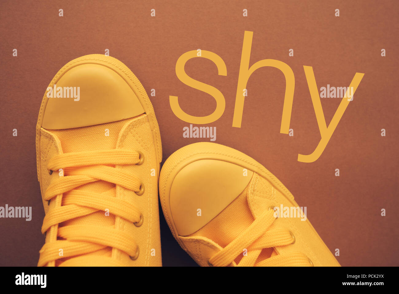 Shy person and shyness, conceptual image with yellow sneakers from above - Stock Image
