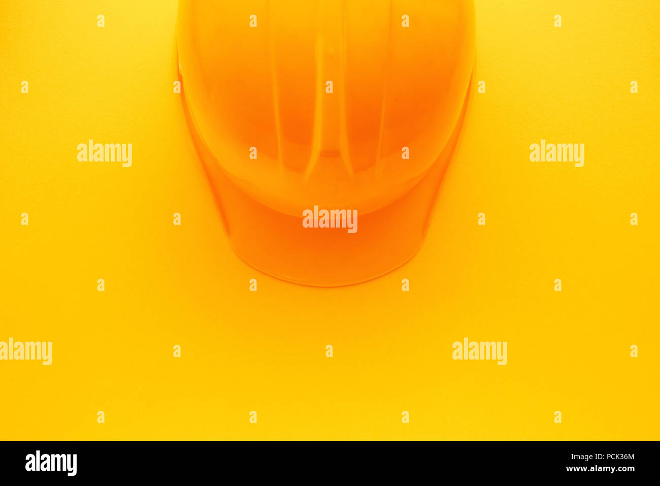 Yellow construction hardhat helmet, protective headgear equipment in building industry - Stock Image