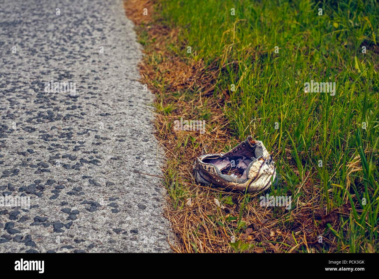 abandoned broken sport shoes on the side of the road - Stock Image