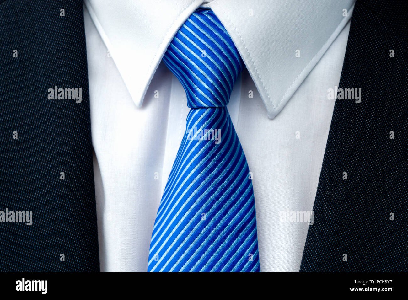 Close-up of a blue striped tie with withe shirt and dark ...