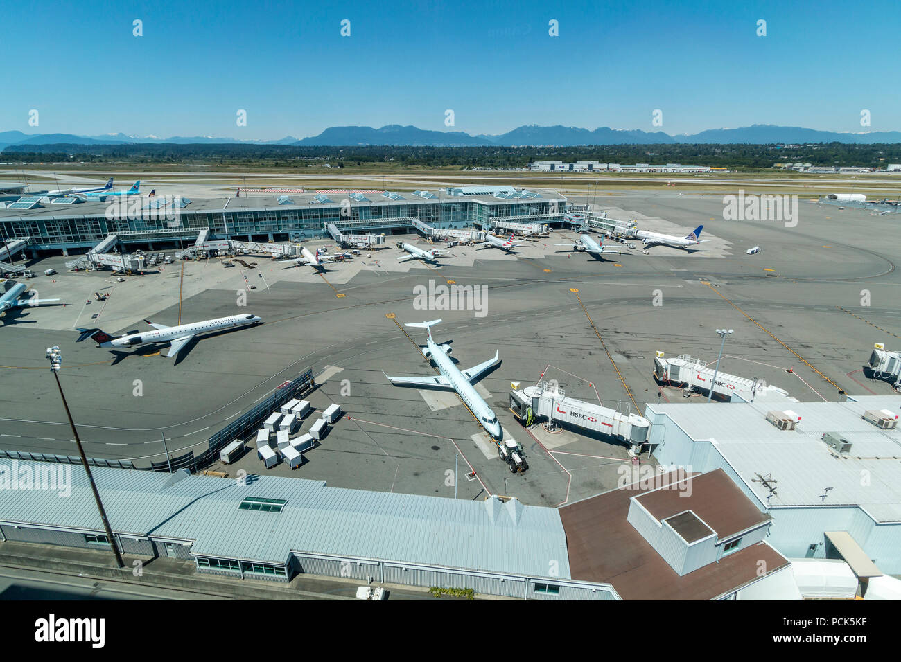 View of jets coming and going at Vancouver International Airport (YVR) from the window of the Fairmont Vancouver Airport hotel located in the airport. - Stock Image