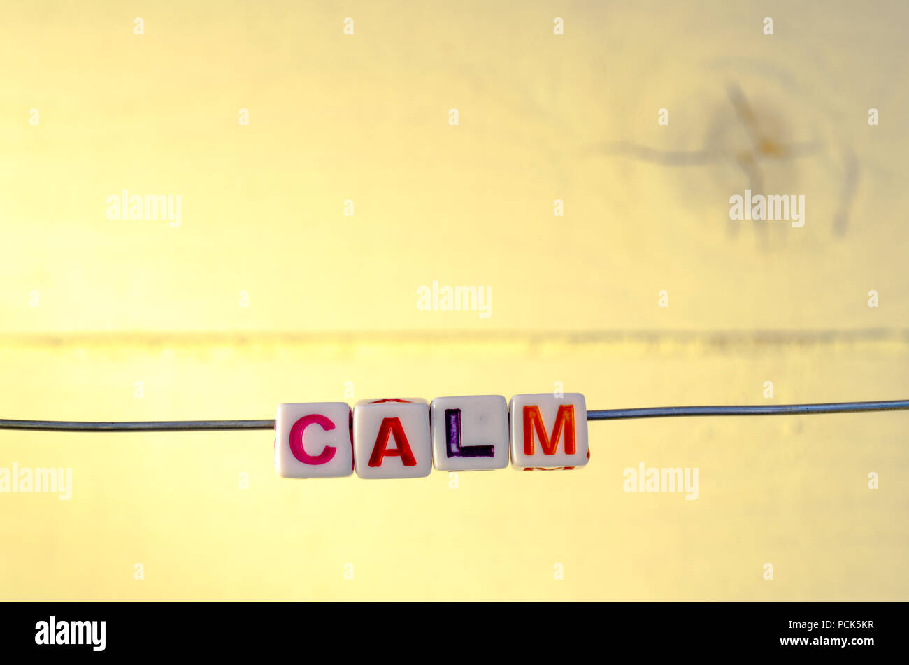 A Studio Photograph of Alphabetical Beads Suspended on a Wire Spelling 'Calm' - Stock Image