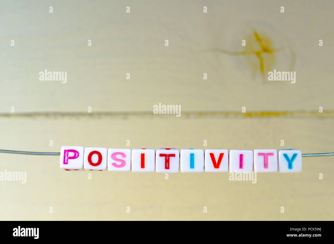 A Studio Photograph of Alphabetical Beads Suspended on a Wire Spelling 'Positivity' - Stock Image