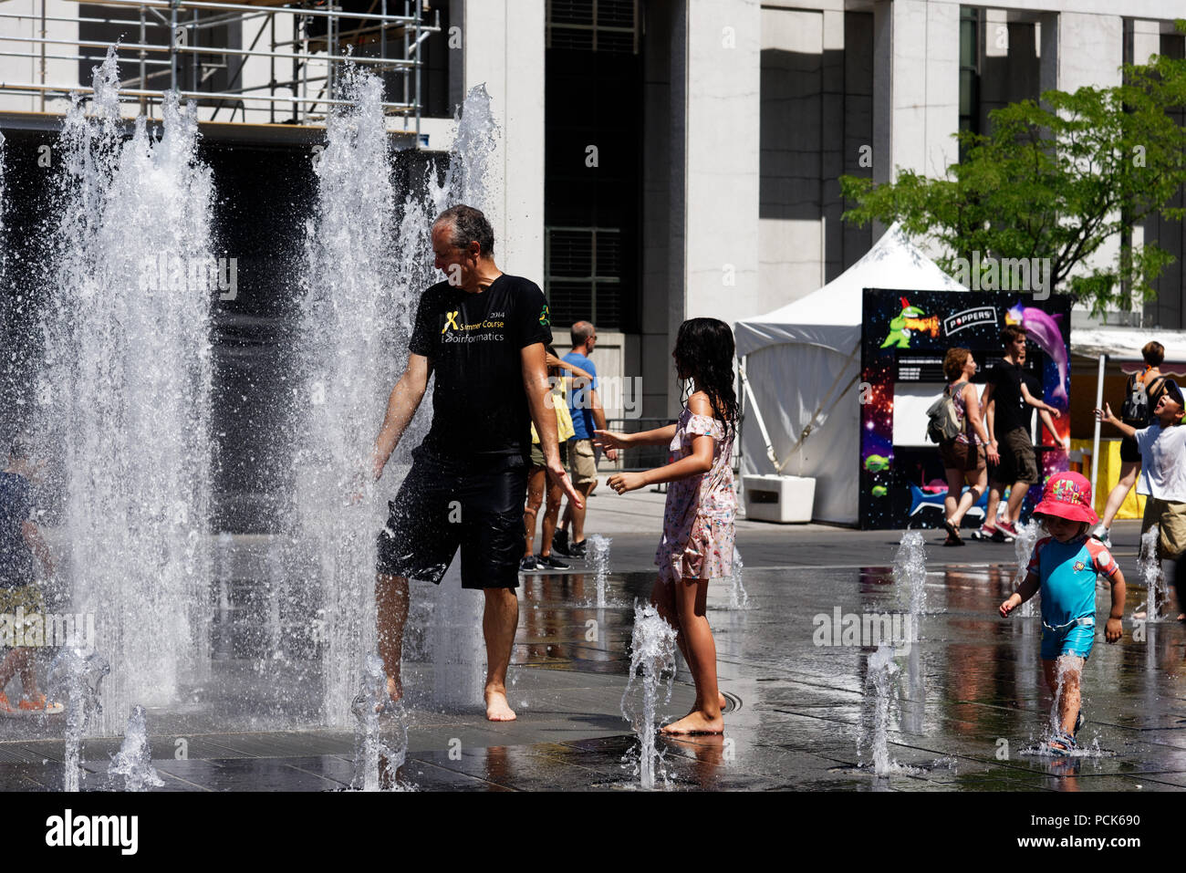 People keeping cool in the water fountains in Montreal in the 2018 heatwave - Stock Image