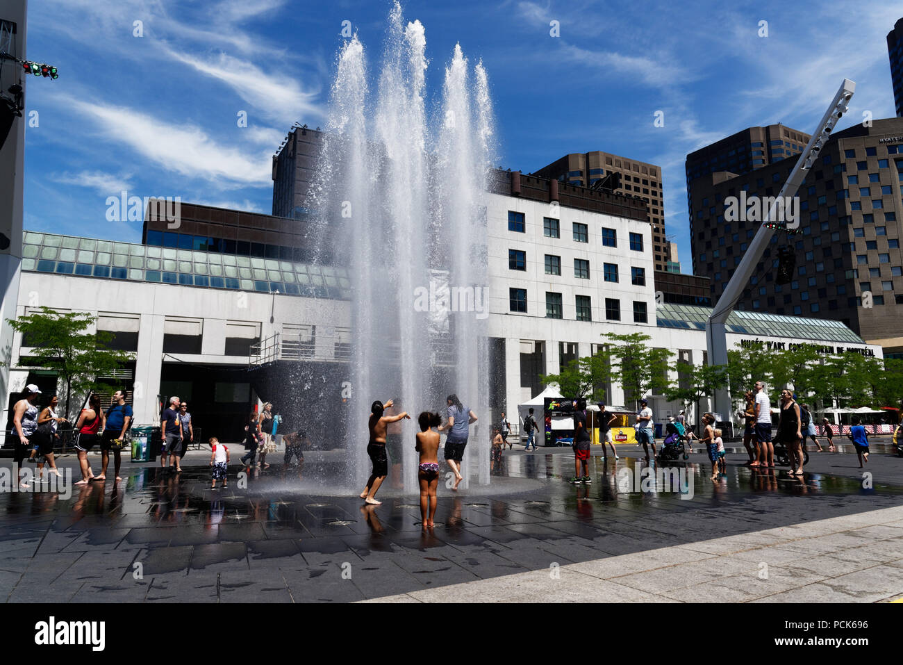 Children cooling off playing in water fountains in on Rue Jeanne Mance in Montreals Entertainment District. Taken during the 2108 heatwave. - Stock Image