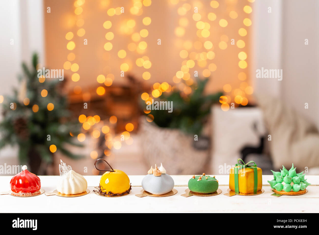 Merry Christmas card. Variety of sweet delicious cakes. Fir branches on a gray background. Merry Christmas card. New year mood - Stock Image