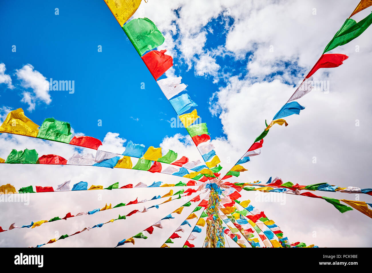 Looking up at Buddhist prayer flags. Tibetans believe the prayers and mantras will be blown by the wind to spread the good will and compassion. - Stock Image