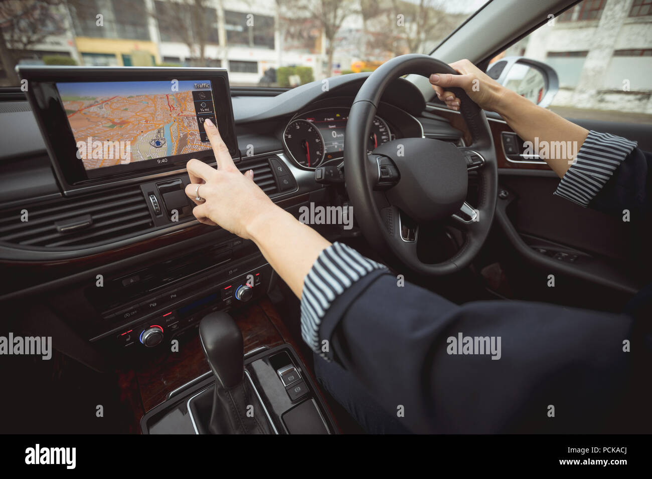 Female executive using navigation while driving a car Stock Photo
