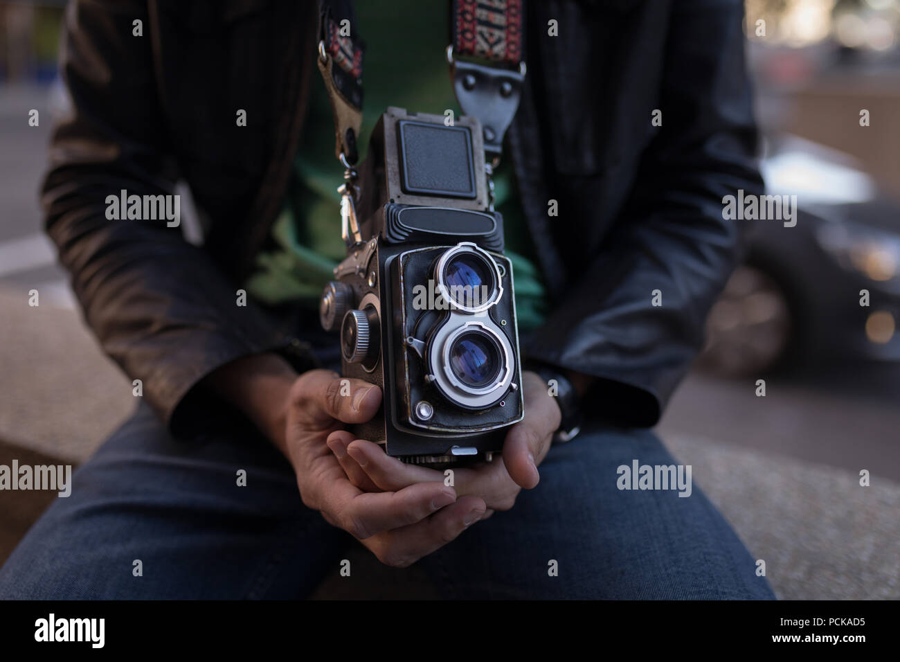 Photographer with camera sitting on surrounding wall near street - Stock Image