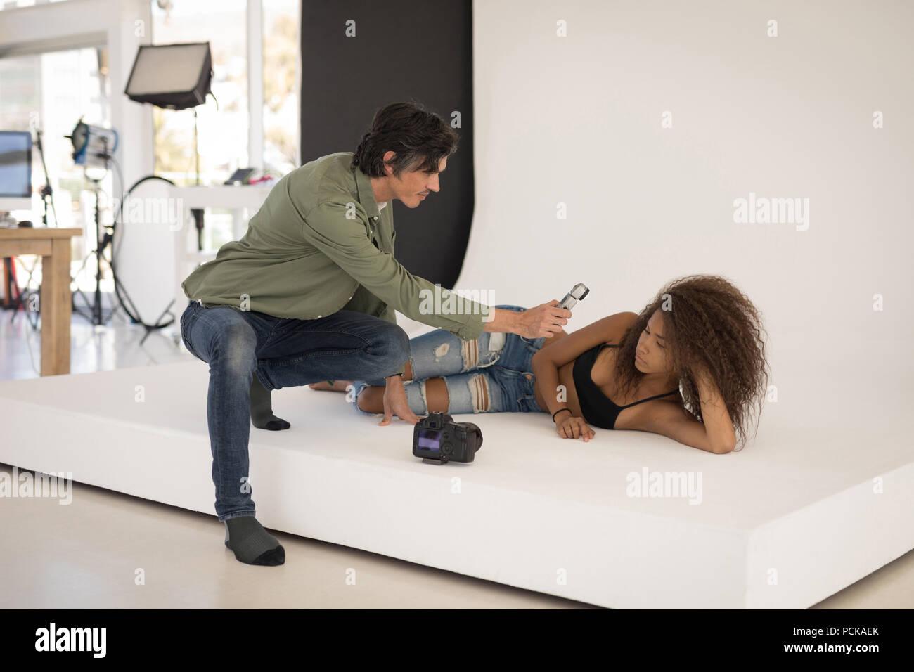 Photographer measuring light with light meter on female model Stock Photo