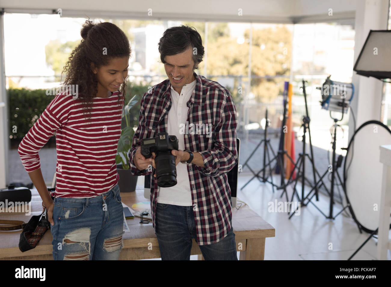 Photographer showing photos to fashion model on digital camera - Stock Image