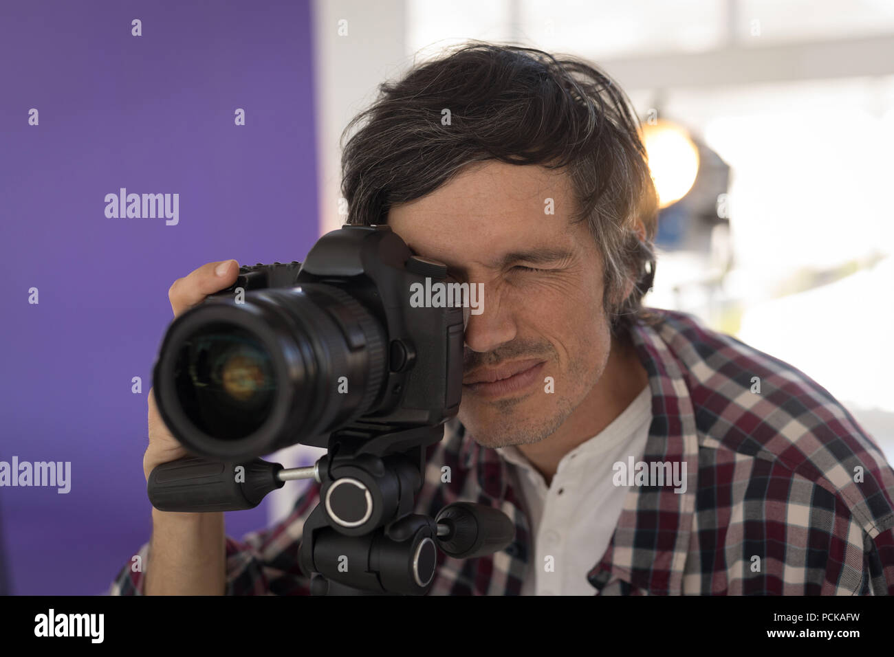 Photographer taking pictures in the studio - Stock Image