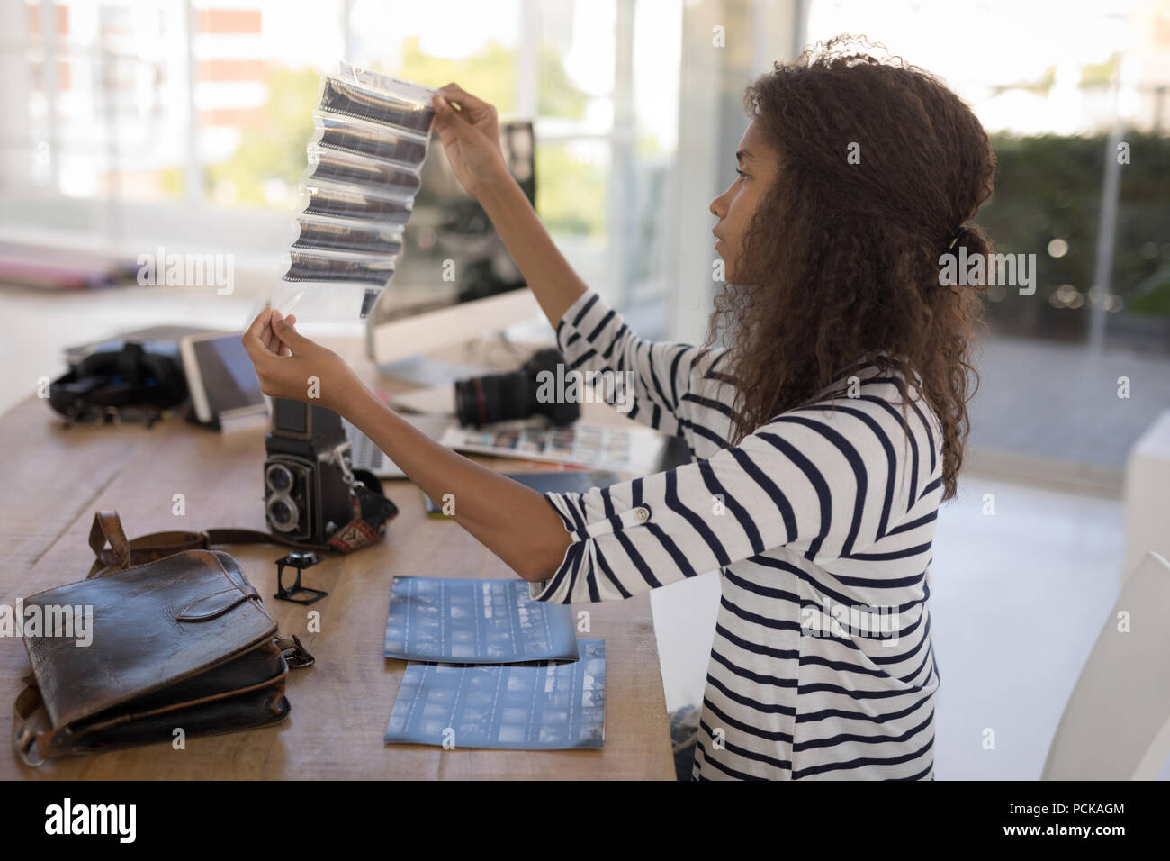 Photographer checking photo negatives at desk - Stock Image