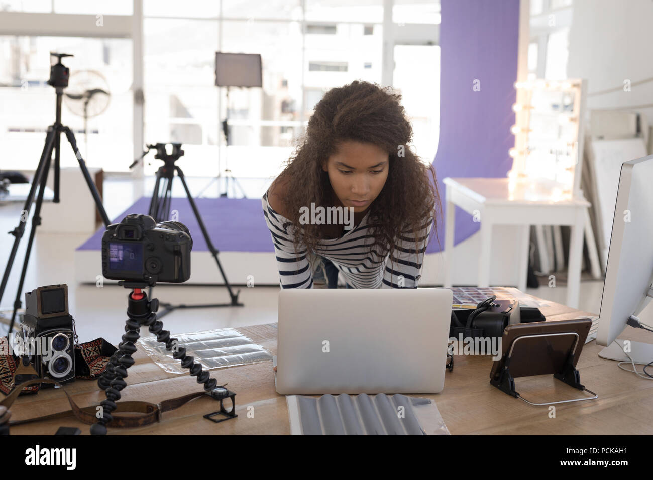 Photographer using laptop at desk - Stock Image