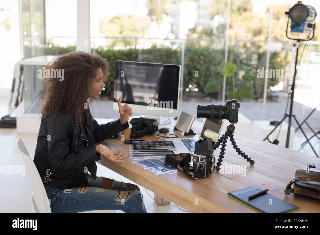 Pretty photographer working at laptop - Stock Image