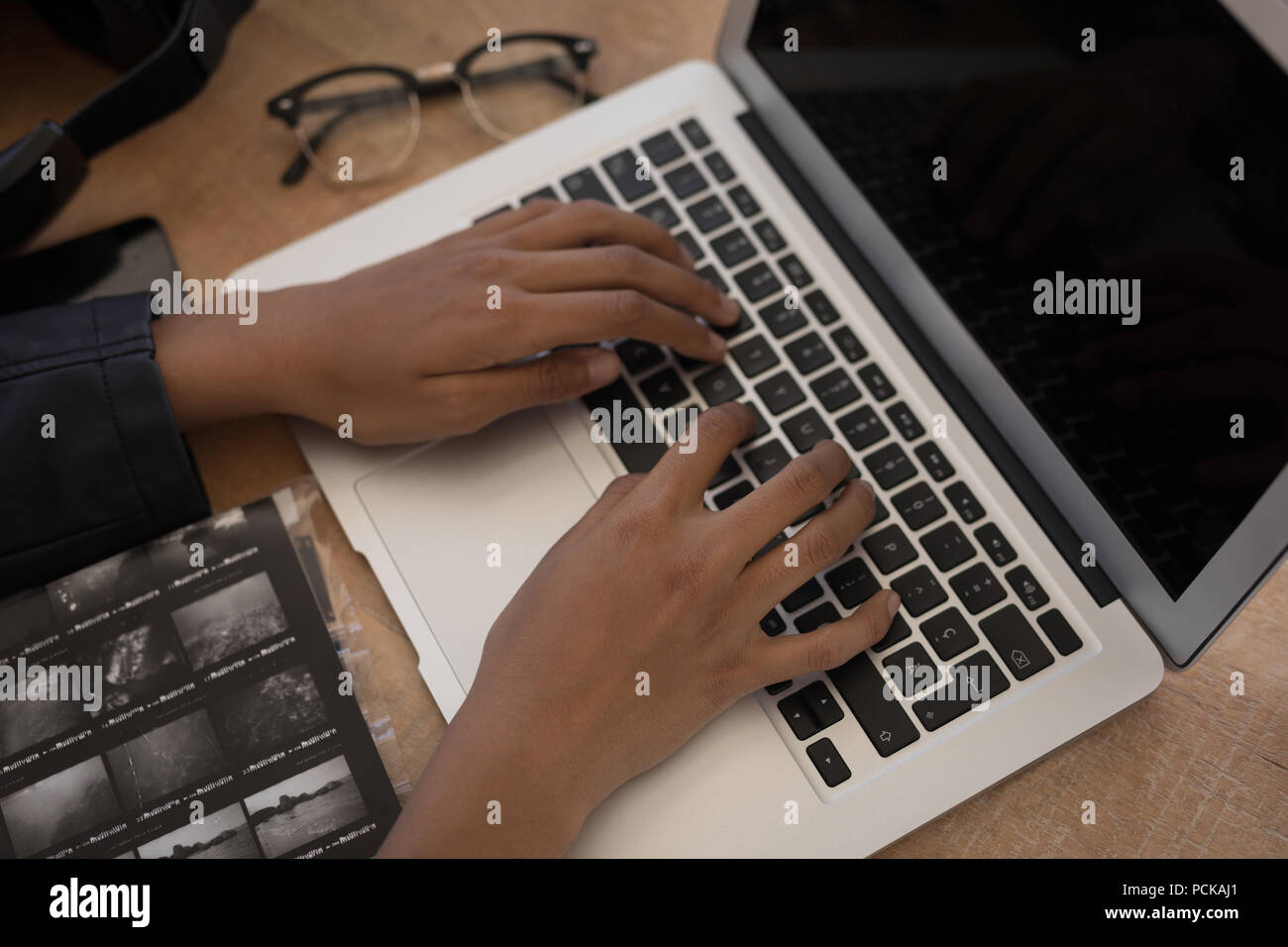 Photographer using laptop on desk Stock Photo