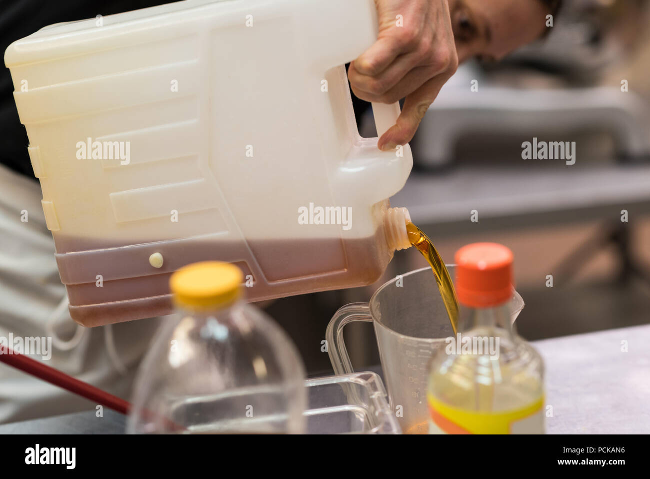 Chef pouring edible oil in a container - Stock Image