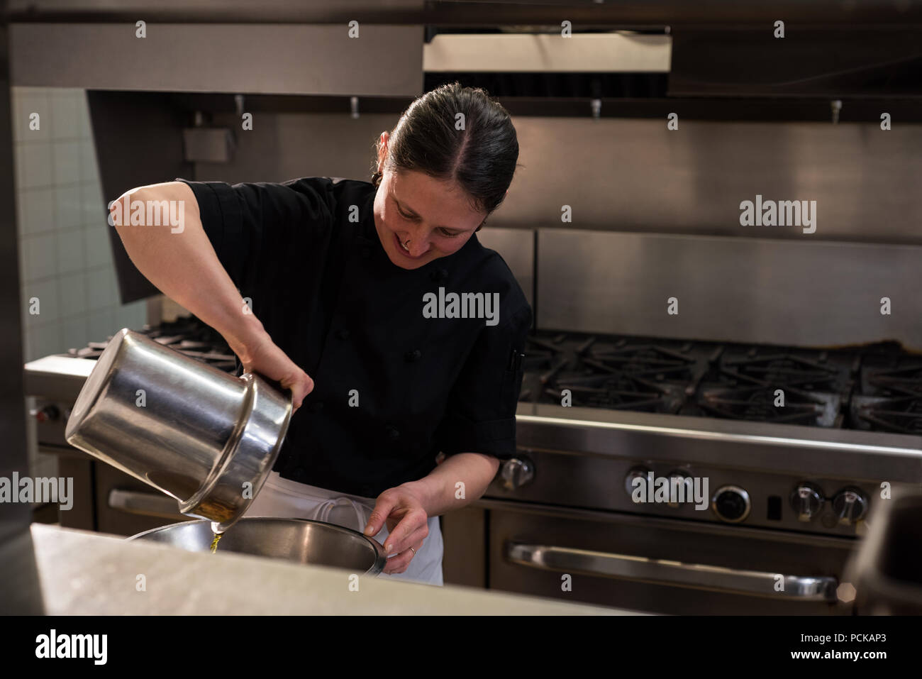 Chef pouring oil into a container - Stock Image