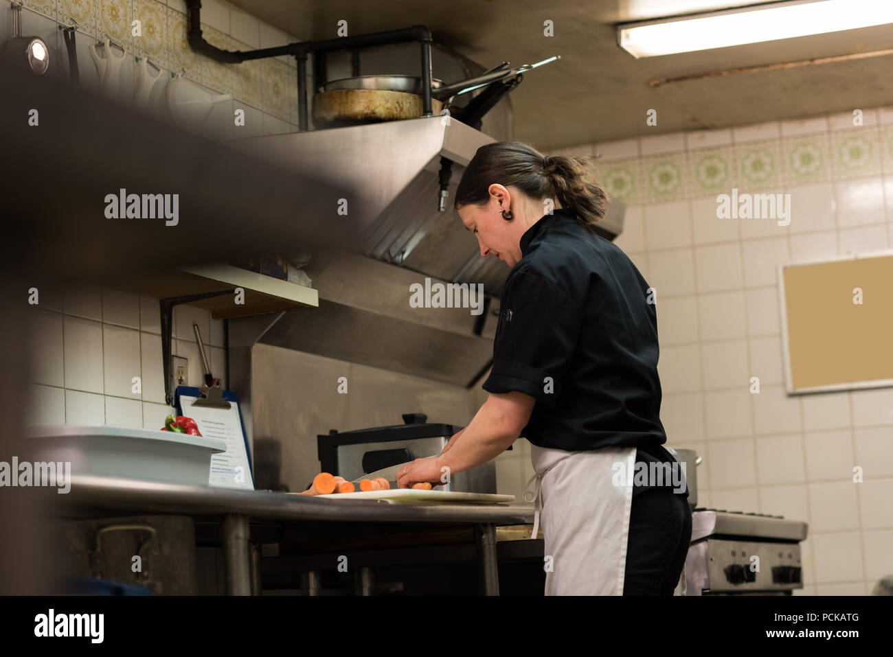Chef chopping vegetables in the commercial kitchen - Stock Image