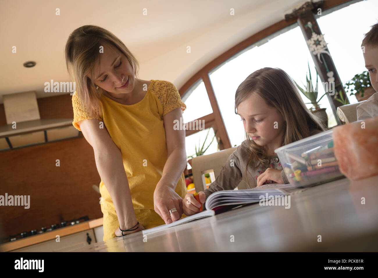 Mother helping children with homework in kitchen - Stock Image