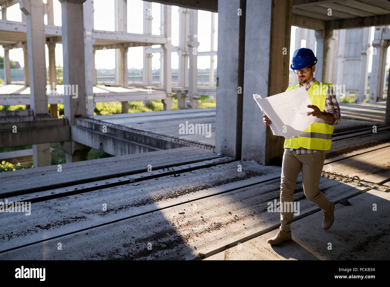 Construction engineer in hardhat with project in hands - Stock Image